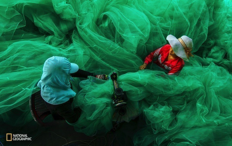 two-women-become-lost-in-the-fabric-of-a-fishing-net-in-vinh-hy-ninh-thuan-vietnam-they-are-sewingthe-net-for-a-new-fishing-season-while-their-husbands-are-out-fishing